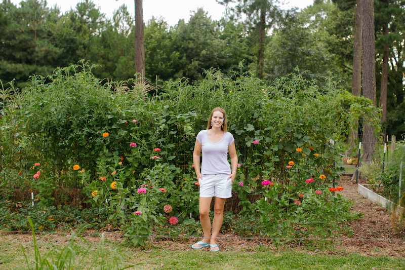 Pretty woman in vegetable and flower garden